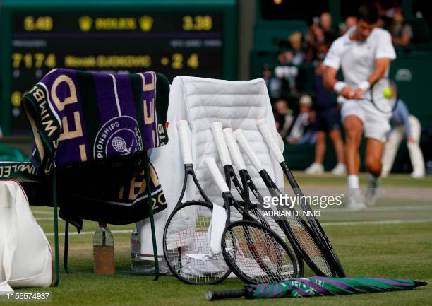 Serbia's Novak Djokovic's racquets are seen in the foreground as he returns against Switzerland's Roger Federer during their men's singles final on...