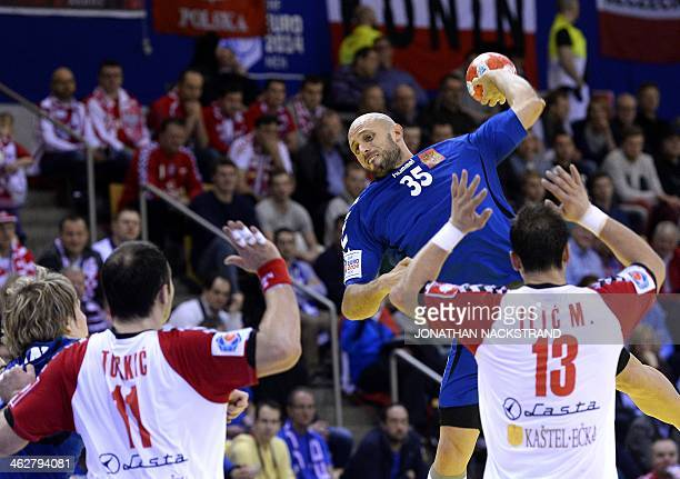 Serbia's pivot Alem Toskic and left back Momir Ilic react as Russia's right back Konstantin Igropulo jumps to score during the men's EHF Euro 2014...