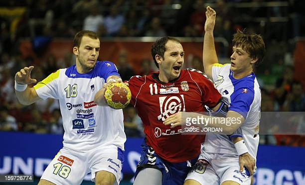 Serbia's pivot Alem Toskic vies with Slovenia's pivot Uros Bundalo and Slovenia's right back Jure Dolenec during the 23rd Men's Handball World...