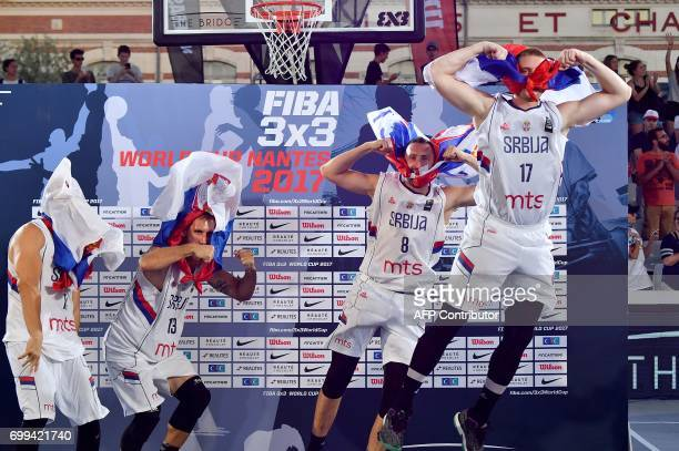 Serbia's players celebrate on the podium after winning the the FIBA 3X3 World Cup semifinal basketball match Slovenia vs Netherlands in Nantes on...