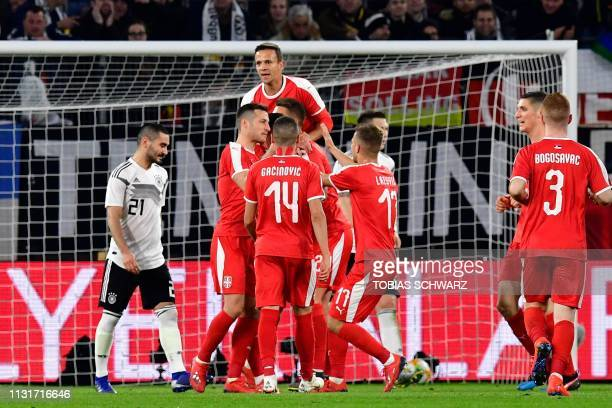 Serbia's players celebrate scoring the opening goal during the friendly football match Germany v Serbia in Wolfsburg western Germany on March 20 2019