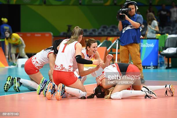 Serbia's players kneel on the court as they react after winning their women's semifinal volleyball match against USA at the Maracanazinho stadium in...