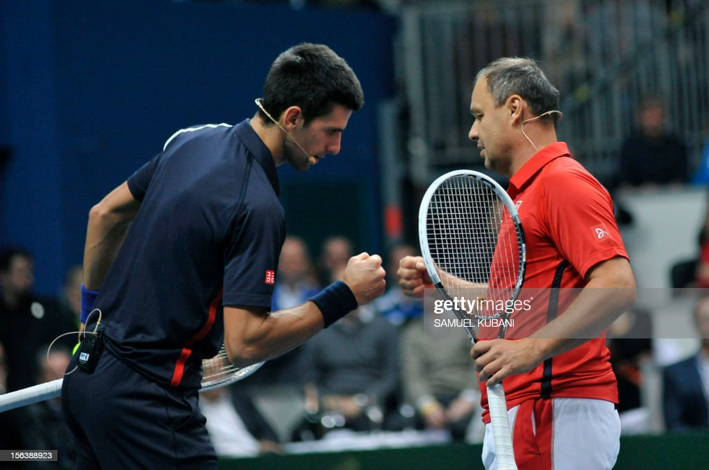 Serbia's tennis player Novak Djokovic (L) cheers with his coach Marian Vajda during a Tennis Classic exhibition match against Slovakian Dominik Hrbaty and Martin Klizan on November 14, 2012 in Bratislava.