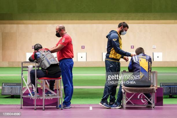 Serbia's Zdravko Savanovic and Ukraine's Vasyl Kovalchuk compete as their assistants look on during the final of the shooting R9 mixed 50m rifle...