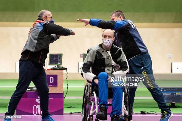 Serbia's Zdravko Savanovic greets Ukraine's Vasyl Kovalchuk over Serbia's Dragan Ristic after competing in the final of the shooting R9 mixed 50m...