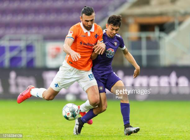 Serdar Dursun of Darmstadt battles for possession with Aues John-Patrick Straus during the Second Bundesliga match between FC Erzgebirge Aue and SV...