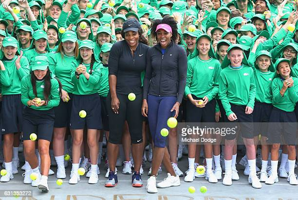 Serena Williams and sister Venus Williams of the USA pose with over 380 Australian Open ballkids for the annual welcome ceremony during a practice...