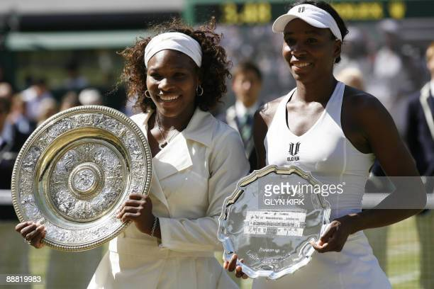 Serena Williams and US Venus Williams hold up their trophies after their women's final match on Day 12 at the 2009 Wimbledon tennis championships at...