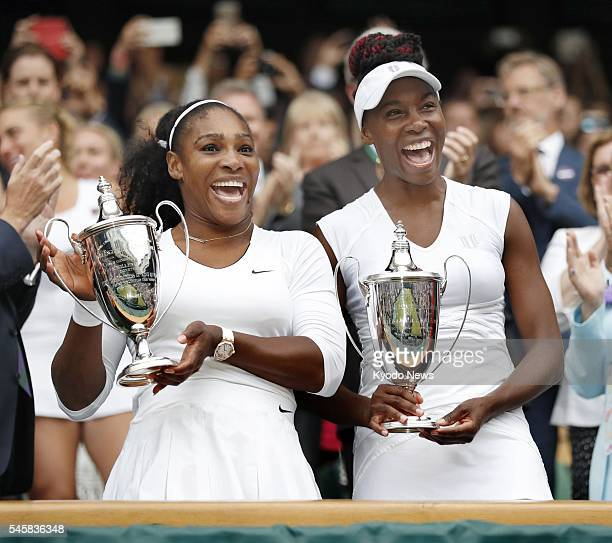 Serena Williams and Venus Williams of the United States pose with the winner's trophies following the women's doubles final at the Wimbledon...