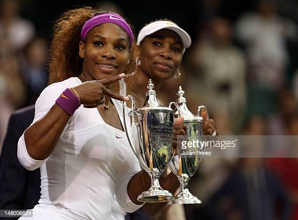 Serena Williams and Venus Williams of the USA celebrate with their winners trophies after their Ladies' Doubles final match against Andrea Hlavackova...