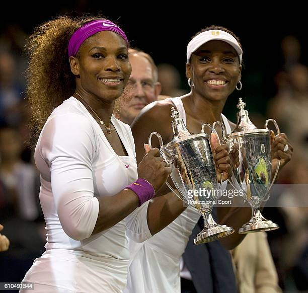 Serena Williams and Venus Williams of the USA celebrate with their winners' trophies after their Ladies Doubles final against Andrea Hlavackova and...