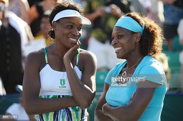 Serena Williams and Venus Williams smile as they converse before the trophy ceremony after winning the doubles final over Yung-Jan Chan of Taipei and...