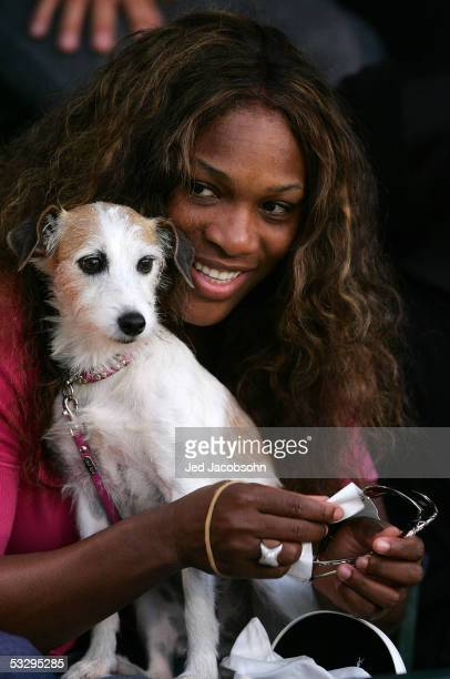 Serena Williams holds her dog Jackie, as her sister Venus Williams of the USA plays against Sania Mirza of India during the Bank of the West Classic...