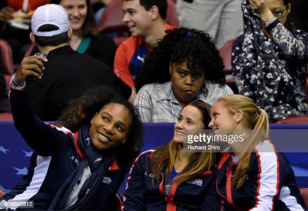 Serena Williams of Team USA bottom left takes a selfie photo with teammates Lauren Davis center and Shelby Rogers during the first round of the 2018...