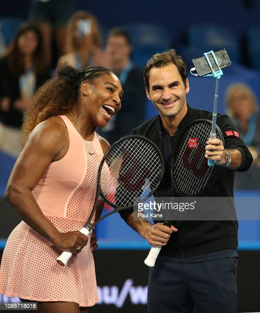 Serena Williams of the United States and Roger Federer of Switzerland take a selfie on court following their mixed doubles match during day four of...