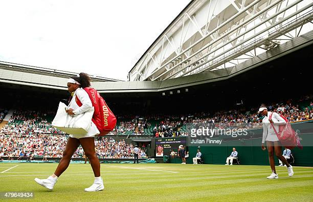 Serena Williams of the United States and Venus Williams of the United States make their way onto Centre Court for their Ladies' Singles Fourth Round...