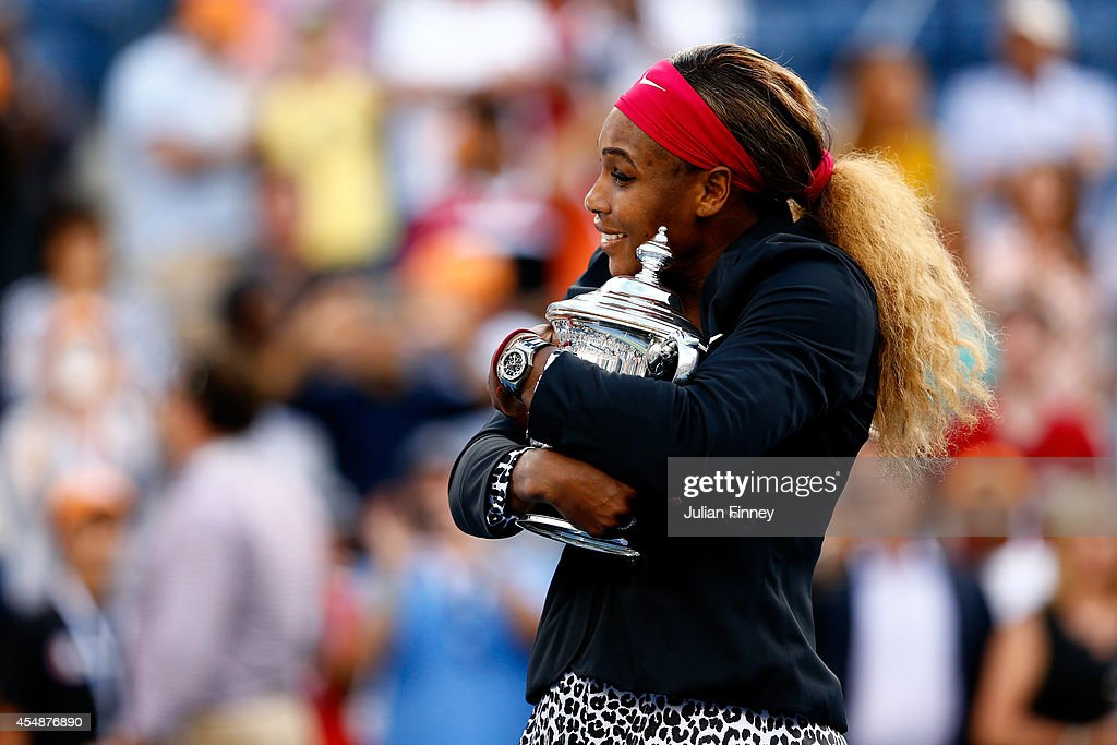 Serena Williams of the United States celebrates with the trophy after defeating Caroline Wozniacki of Denmark to win their women's singles final match on Day fourteen of the 2014 US Open at the USTA Billie Jean King National Tennis Center on September 7, 2014 in the Flushing neighborhood of the Queens borough of New York City. Williams defeated Wozniacki in two sets by a score of 6-3, 6-3.