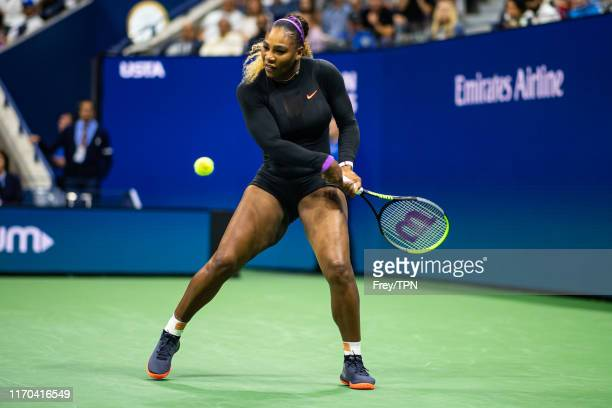 Serena Williams of the United States hits a backhand against Maria Sharapova of Russia in the first round of the US Open in Arthur Ashe Stadium at...