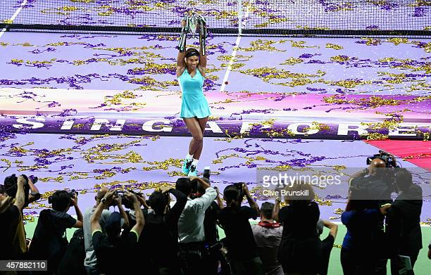 Serena Williams of the United States holds aloft the Billie Jean King Trophy as she poses for photographers after her straight sets victory against...