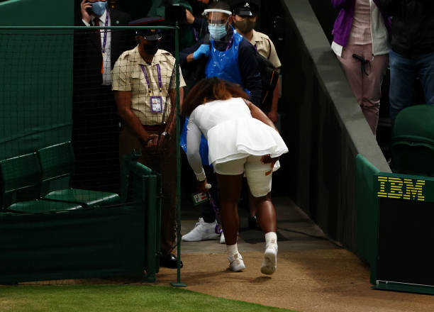 Serena Williams of The United States holds her leg as she walks off the court after retiring from her Ladies' Singles First Round match against...