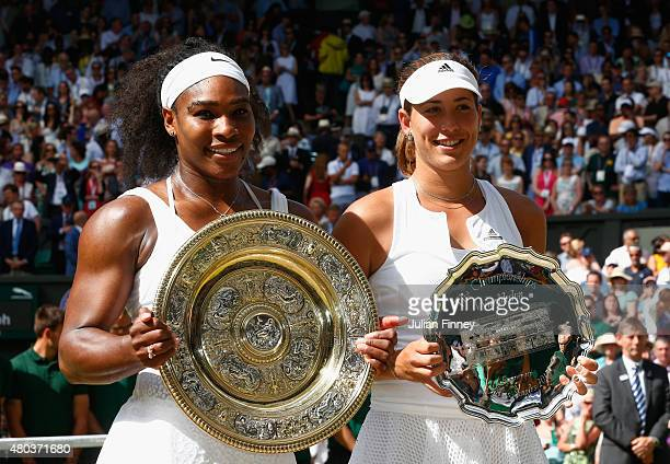 Serena Williams of the United States holds the Venus Rosewater Dish next to Garbine Muguruza of Spain holding the runners up trophy after her victory...