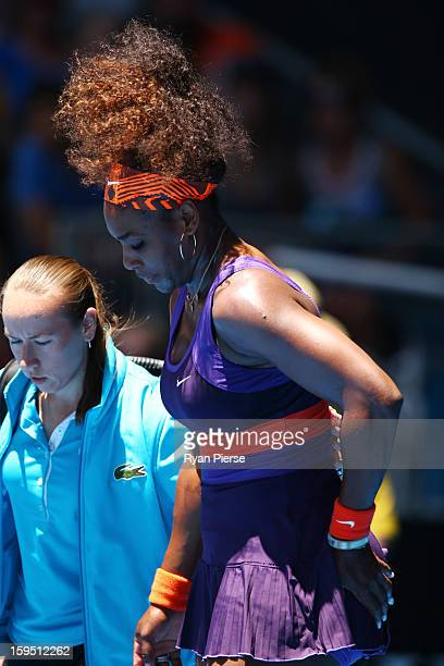 Serena Williams of the United States is assisted from the court after falling onto the court injuring her ankle in her first round match against...