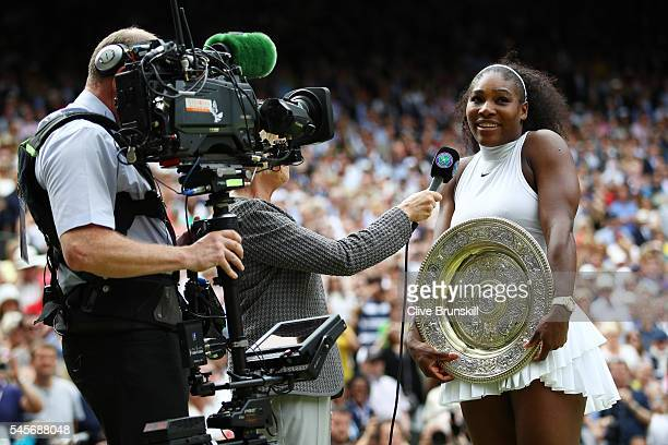 Serena Williams of The United States is interviewed by Sue Barker as she holds the trophy following victory in The Ladies Singles Final against...