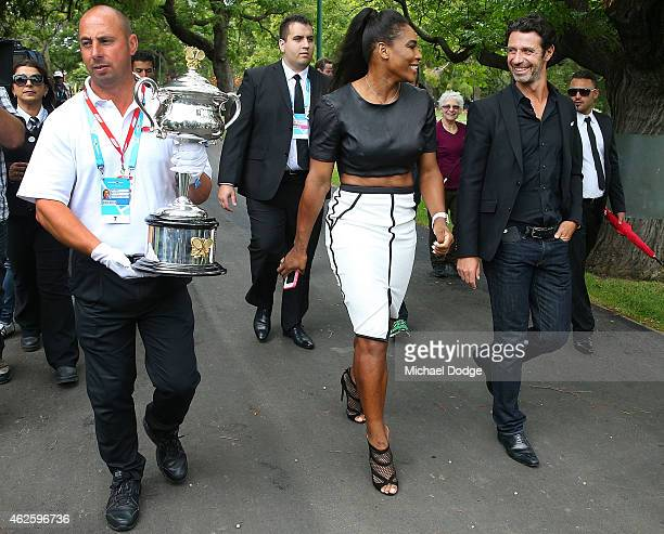 Serena Williams of the United States leaves with her partner and coach Patrick Mouratoglou and the Daphne Akhurst Memorial Cup during a photocall at...