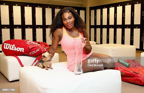 Serena Williams of the United States poses for a photgraph with the Butch Bucholz Trophy in the locker room after her straight sets victory against...