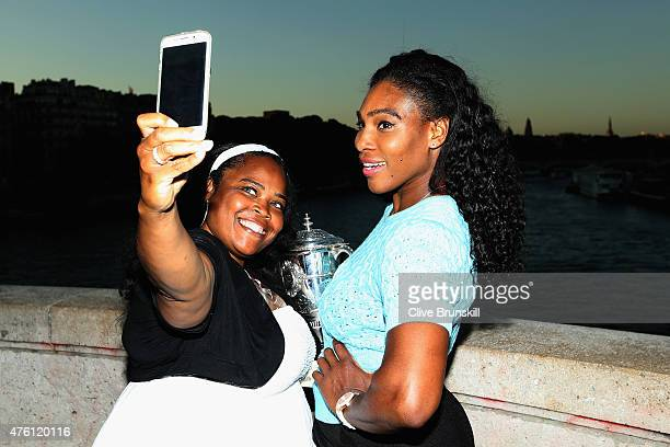 Serena Williams of the United States poses with the Coupe Suzanne Lenglen trophy and her sister Isha Price on day fourteen of the 2015 French Open at...