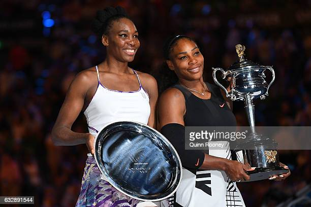 Serena Williams of the United States poses with the Daphne Akhurst Trophy alongside Venus Williams of the United States after the Women's Singles...