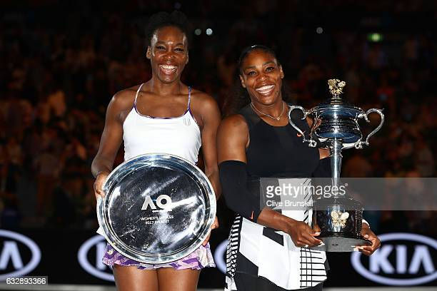 Serena Williams of the United States poses with the Daphne Akhurst Trophy alongside Venus Williams of the United States, posing with the runners up...