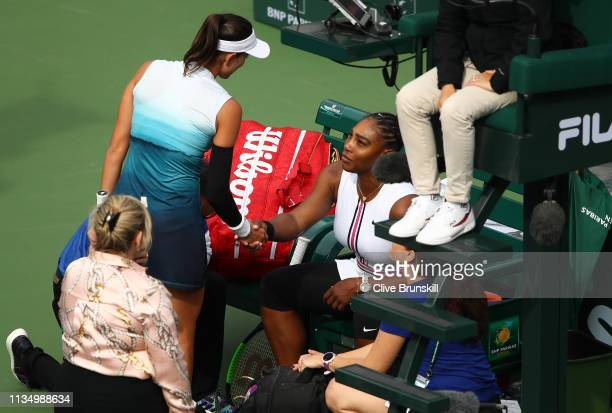Serena Williams of the United States shakes hands after retiring from her match in at the start of the second set against Garbine Muguruza of Spain...