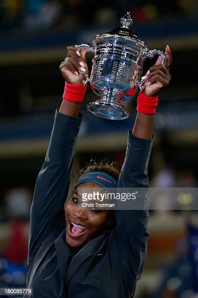 Serena Williams of the United States smiles as she poses with the trophy after winning her women's singles final match against Victoria Azarenka of...