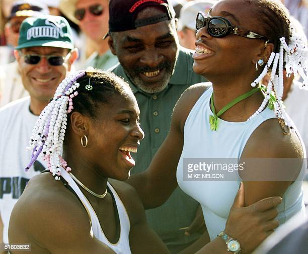Serena Williams of the US celebrates her Evert Cup final victory over Steffi Graf of Germany with her sister Venus and her father Richard 13 March...