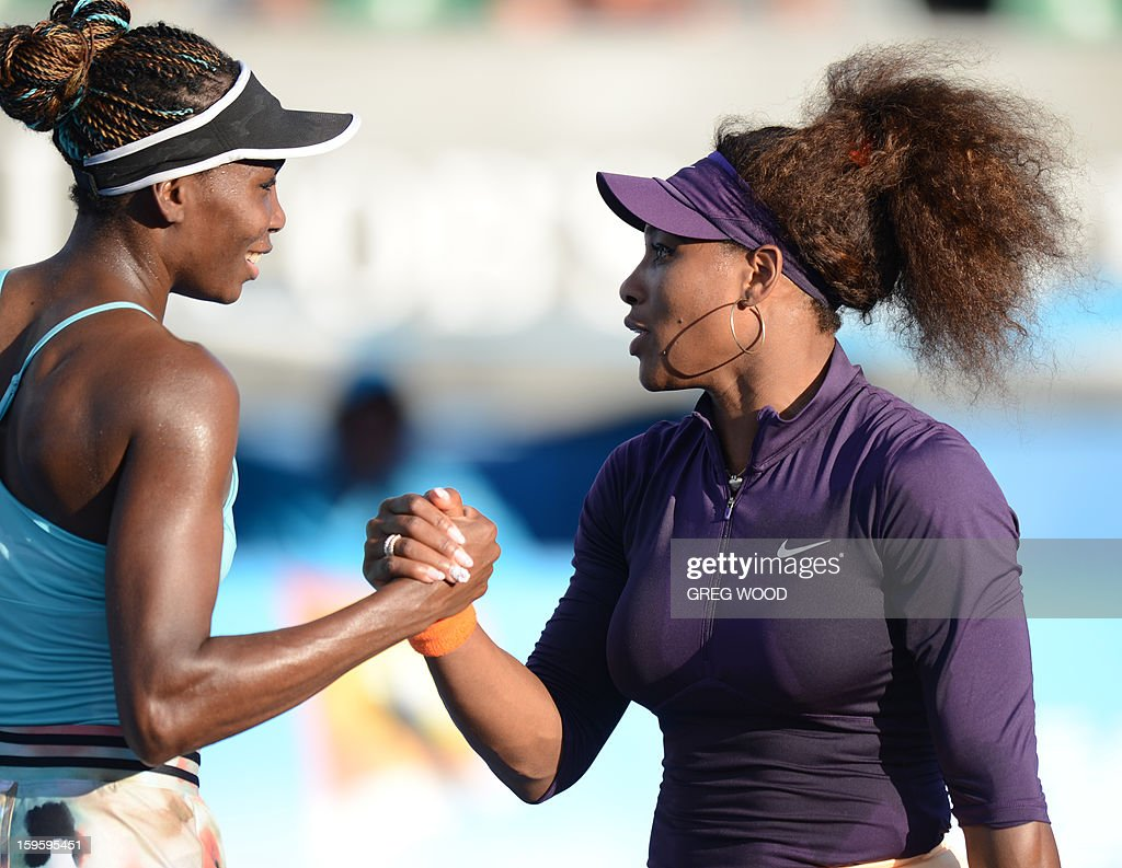 Serena Williams of the US (R) congratulates her sister Venus Williams after victory in their women's doubles match against Camila Giorgi of Italy and Stefanie Voegele of Switzerland on the fourth day of the Australian Open tennis tournament in Melbourne on January 17, 2013.