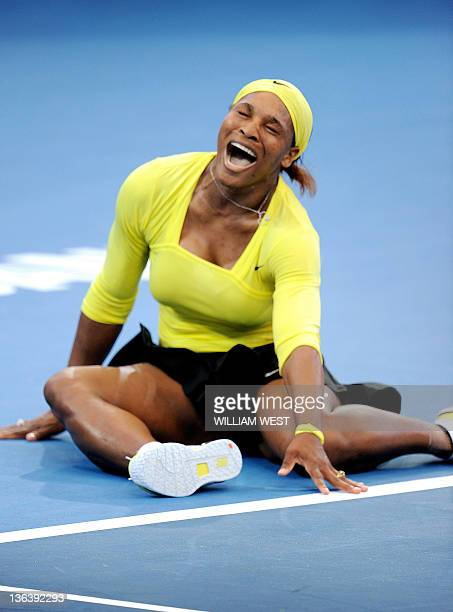 Serena Williams of the US falls to the ground after injuring her ankle during her second round women's singles match against Bojana Jovanovski of...