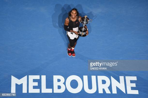TOPSHOT Serena Williams of the US holds the championship trophy after her victory in the women's singles final match against Venus Williams of the US...