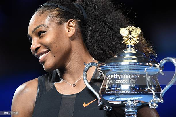 Serena Williams of the US holds up the trophy following her victory over Venus Williams of the US in the women's singles final on day 13 of the...