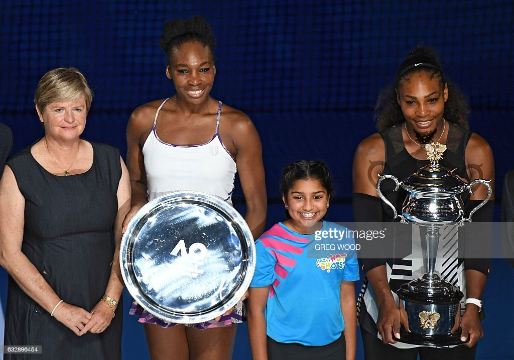 Serena Williams of the US (R) holds up the winner's trophy at the awards ceremony following her victory over Venus Williams of the US (2nd L) in the women's singles final on day 13 of the Australian Open tennis tournament in Melbourne on January 28, 2017. / AFP / Greg Wood / IMAGE