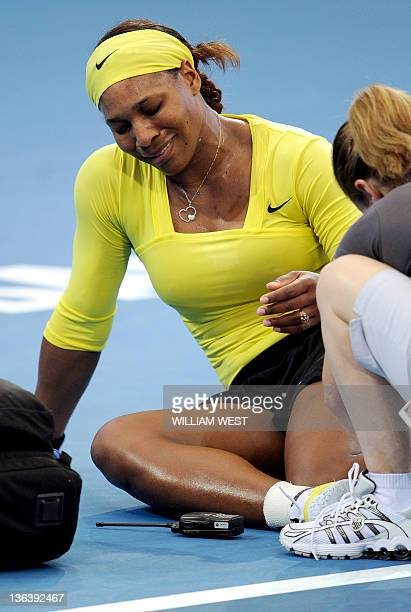 Serena Williams of the US receives treatment after injuring her ankle during her second round women's singles match against Bojana Jovanovski of...