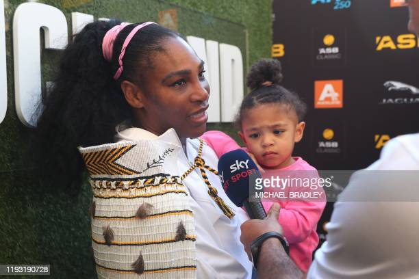 Serena Williams of the US with her daughter Alexis Olympia give an interview after her win against Jessica Pegula of the US during their women's...
