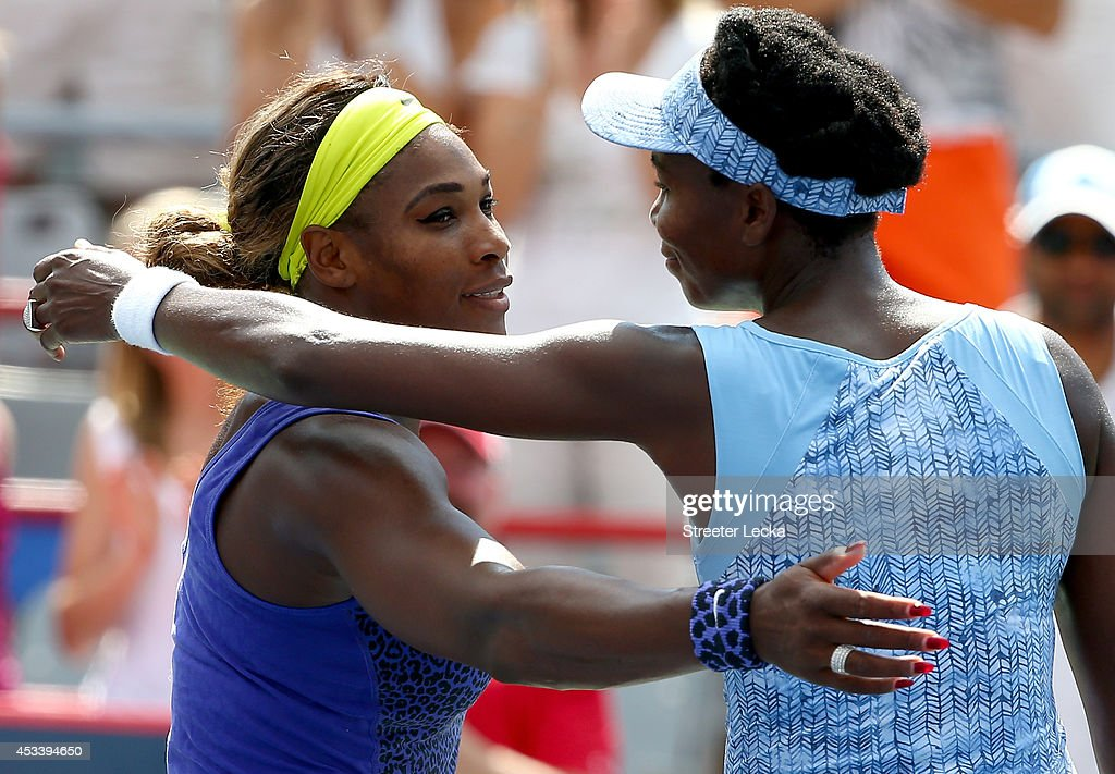Serena Williams of the USA and Venus Williams of the USA hug after the match in which Venus won during the women's semifinals match in the Rogers Cup at Uniprix Stadium on August 9, 2014 in Montreal, Canada.
