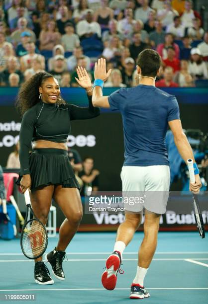 Serena Williams of the USA high fives Novak Djokovic of Serbia during the Rally for Relief Bushfire Appeal event at Rod Laver Arena on January 15...