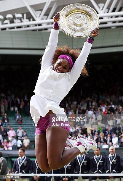 Serena Williams of the USA jumps in the air with the winners trophy and celebrates after her Ladies' Singles final match against Agnieszka...