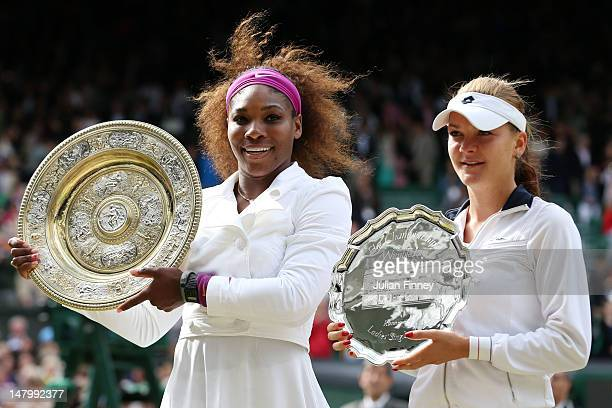 Serena Williams of the USA lifts the winners trophy alongside runnerup Agnieszka Radwanska of Poland after their Ladies' Singles final match on day...