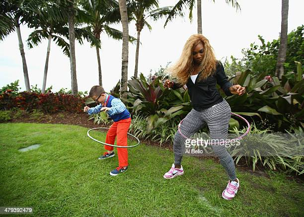 Serena Williams of the USA swings a hula Hoop with Frankie Sanchez of the Miami Cub Reporter during the Sony Open at Crandon Park Tennis Center on...