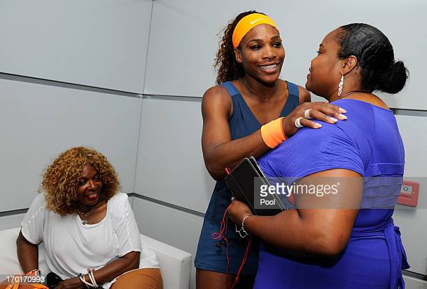 Serena Williams of United States of America hugs Isha Price in her changing room as Oracene Price looks on after her women's singles final match...
