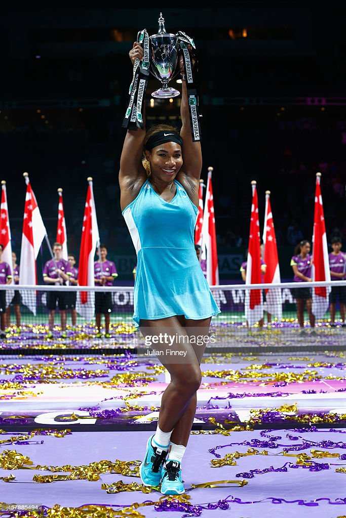 Serena Williams of USA celebrates with the Billie Jean King trophy after she defeats Simona Halep of Romania in the final during day seven of the BNP Paribas WTA Finals tennis at the Singapore Sports Hub on October 26, 2014 in Singapore.