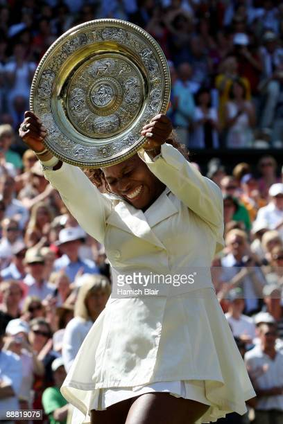 Serena Williams of USA celebrates with the Championship trophy after the women's singles final match against Venus Williams of USA on Day Twelve of...